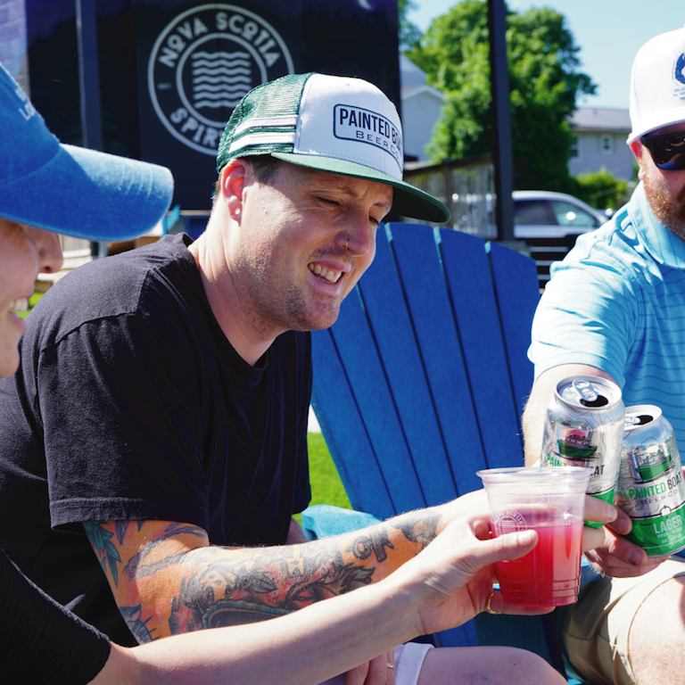 A man enjoying a Painted Boat Lager while wearing a snapback cap with Painted Boat Beer text
