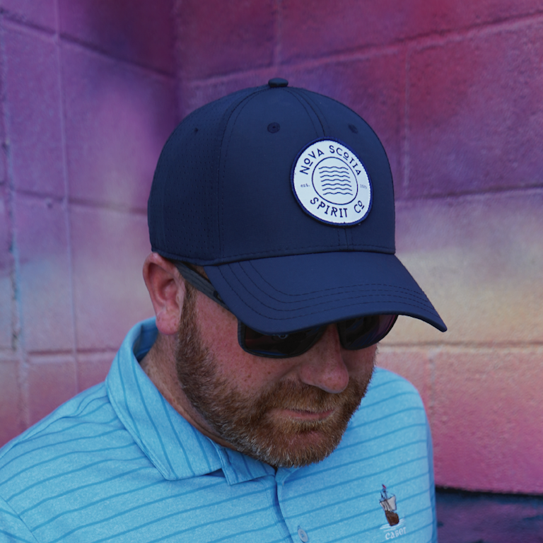 Man wearing a navy blue snapback cap with the Nova Scotia Spirit Co logo on the front